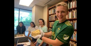 Buchanan Fellow holds artifact from Special Collections