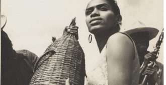 Delia Zapata Olivella holds a wicker-covered bottle