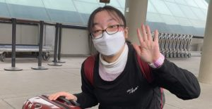 masked student waving in airport